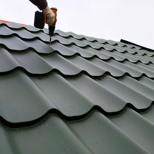 A Roofer Installs Metal Tiles.