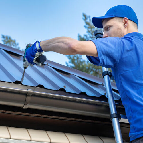 A Roofer Installs Metal Roofing Panels.