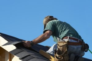 a roofer laying down shingles on a roof, re-roofing