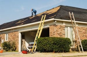 roofer reroofing a brick home