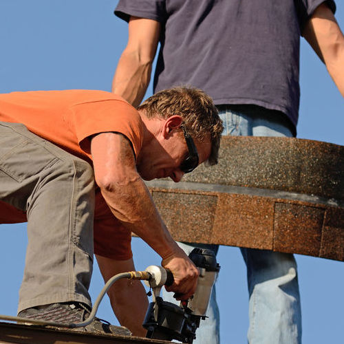 A Roofer Adds Shingles to a Roof With a Nail Gun.
