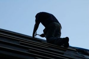 a roofer at dusk, our residential roofing company is on call