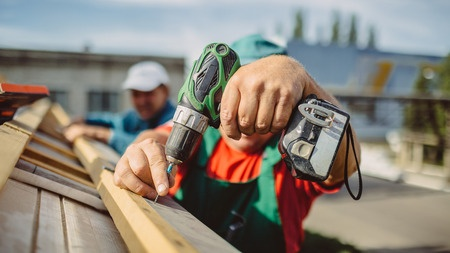 a roofer using a drill, about us