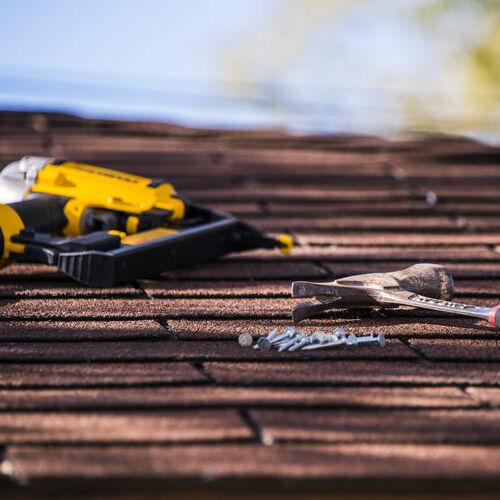 A Nail Gun, Hammer, and Nails On a Shingle Roof.