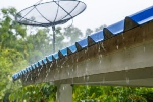 Corrugated Metal Roofing With Rain Falling Off the Bottom